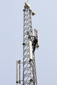 Cell tower technician climbing tower